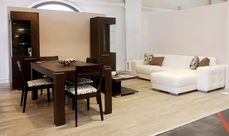 An image of a modern living room, with brown table and white sofa.
