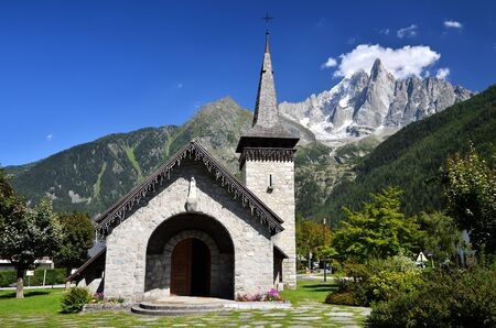 Les Praz de Chamonix medieval church and Aiguille Dru mountain in Alps photo