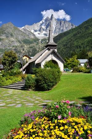 Les Praz de Chamonix medieval church and Aiguille Dru mountain in Alps photo