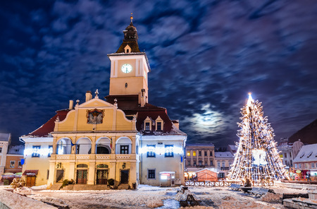 nightshot: Brasov, Romania. Council Square and Xmas Tre. Historical medieval old city center square of Brasov in Christmas days.