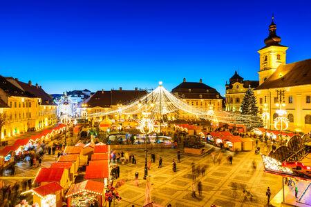 SIBIU, ROMANIA - 20 DECEMBER 2014: Night image with tourists at Christmas Market in Great Market of medieval Sibiu, Transylvania landmark.