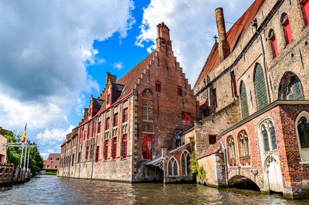 patronage: Bruges Brugge Belgium. Summer scenery with gothic style houses of SintJanshospitaal and water canal in medieval belgian city from Flanders.
