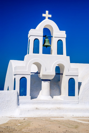 greek islands: Santorini, Greek Islands. Architecture detail with white walls, church cross, bell and blue sky in Thira island of Aeagean Sea in Greece