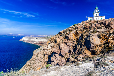greek islands: Santorini, Greece. Akrotiri Lighthouse on the southern of Thira island in Greek Islands on a clear, sunny day with bright, blue sky.
