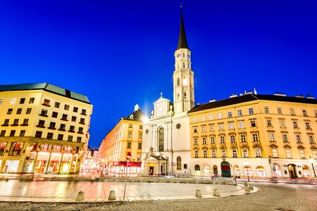 habsburg: Vienna, Austria. Michaelerplatz, wide-angle view at dusk with Michaelkirche, Habsburg Empire landmark in Wien