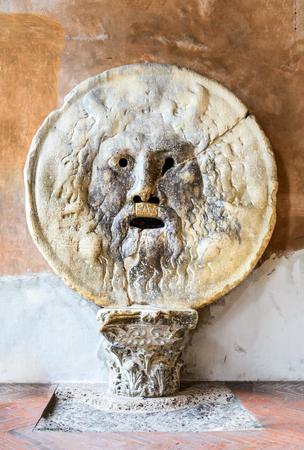 Rome, Italy. The Mouth of Truth (La Bocca della Verita) carved from Pavonazzo marble, in the portico of the church of Santa Maria in Cosmedin.