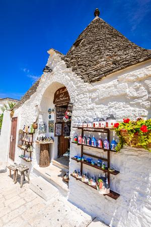 ALBEROBELLO, ITALY - 10 JULY 2015: Alberobello, UNESCO heritage city in Italy, Puglia. Trulli or Trullo houses with conical roofs,  traditional Apulian dry stone hut.
