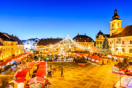 SIBIU, ROMANIA - 20 DECEMBER 2014: Night image with tourists at Christmas Market in Great Market of medieval Sibiu, Transylvania landmark.