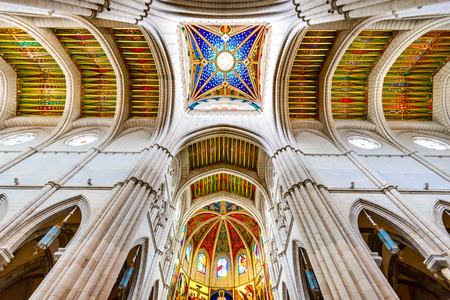 MADRID, SPAIN - NOVEMBER 4, 2015: Symmetrical view of beautifully lit Santa Maria la Real de La Almudena cathedral colourful decorated ceiling with windows from below. Editorial