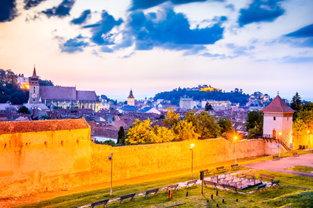Brasov, Romania - Twilight image with medieval city walled fortifications, Black Church and the Citadel in Transylvania. Stock Photo