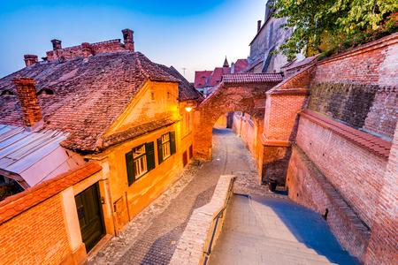 Sibiu, Romania - Passaggio delle scale e la cattedrale luterana al crepuscolo. Città del sassone Transilvania. Archivio Fotografico - 85347367