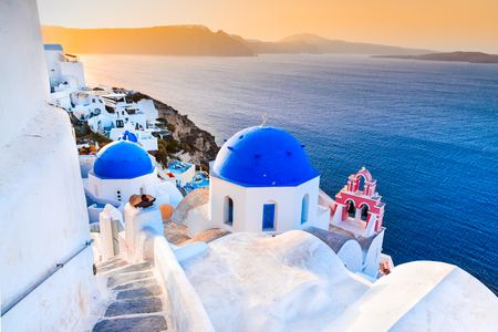 Santorini, Greece. Oia, white village with cobbled narrow paths, famous attraction of Greek Cyclades Islands, Aegean Sea.