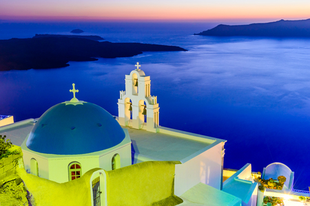 Santorini, Greece. Firostefani twilight with old greek church and caldera at Aegean Sea.