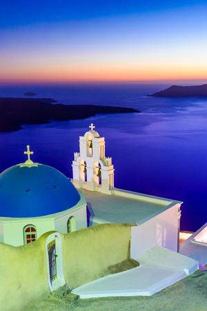 Santorini, Greece. Firostefani twilight with old greek church and caldera at Aegean Sea.