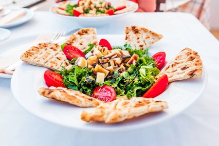 Lindos Salada, local cuisine from Rhodes Island, Greece with pita, cherry tomatoes and parmezan.