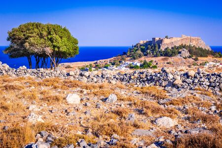 Rhodes, Greece. Lindos small whitewashed village and the Acropolis, scenery of Rhodos Island at Aegean Sea. Imagens