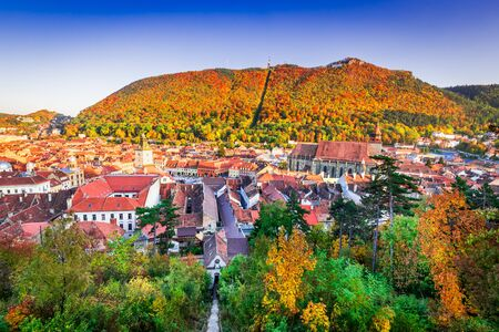 Brasov, Romanian with autumn sunny colors on medieval Transylvania and Carpathian Mountains range. 写真素材