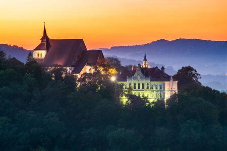 Sighisoara, Romania - Autumn stunning sunset sky over medieval city in Transyilvania. Stock Photo