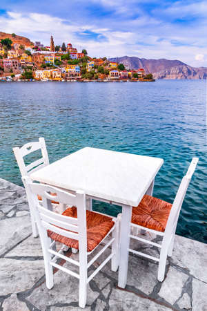 Symi, Dodecanese islands of Greece. White chairs with tables in typical Greek tavern near the sea in Rhodes.