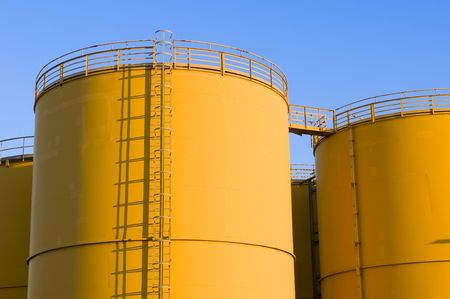 Yellow tanks as part of a large production facility.