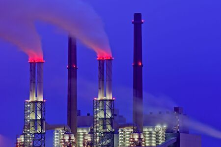 vapour: Red smoke coming from industrial chimneys at night