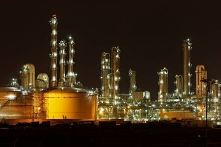 Towers and silos of a chemical production facility at night