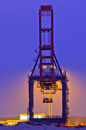 Backlit container crane in the Port of Rotterdam against blue night sky Stock Photo