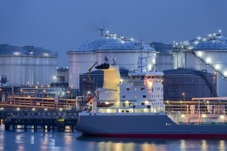 Liquid Natural Gas storage tanks and tanker at dusk, Port of Rotterdam