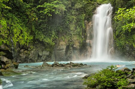 Beautiful Rio Celeste Falls with swimmer, Tenorio National Park, Costa Rica.