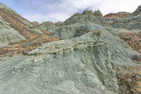 The John Day Basin is a fossil record that spans over 40 million years. The predominant exposures of green rock seen on Sheep Rock are a multitude of reworked layers of volcanic ash. The rich green color of the claystone was caused by chemical weathering of a mineral called celadonite. This happened millions of years ago as water moved through the alkaline ash beds under high pressure.