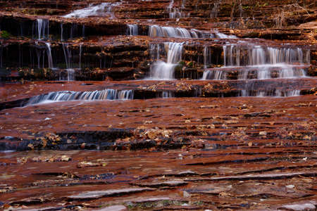 Beautiful waterfall streaming over red colored bedrock in the Left Fork North Creek, Zion National Park.
