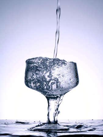 shot of liquid falling into a full glass photo