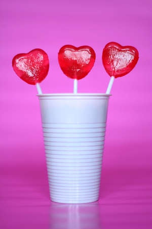lick: heart shaped lollipops in a plastic cup