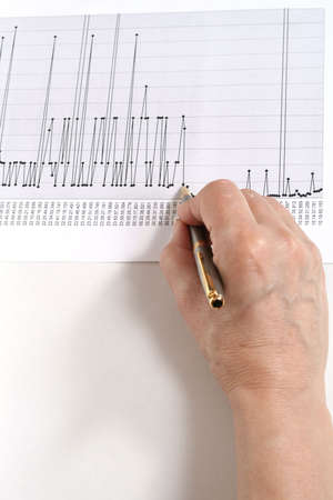 financially: hand with a pen over a chart