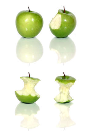 biten: four green apples and apple cores over white