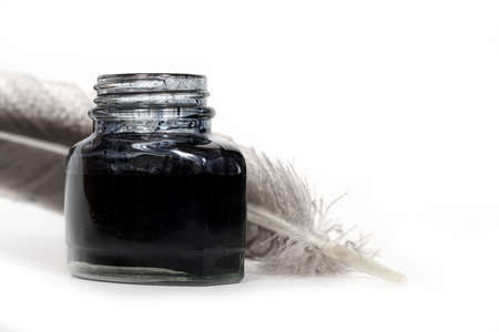 feather quill and inkwell over white background photo