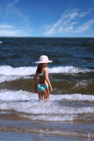 a little lady in a hat standing in the sea photo