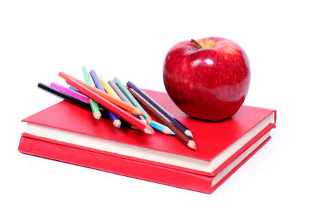 back to school - red apple and colored pencil on red books (isolated on white background)