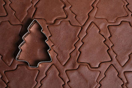 Christmas tree cookie cutter on a sheet of cookie dough photo