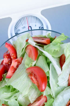 on diet - fresh lettuce and tomatoes in a glass bowl on a scale