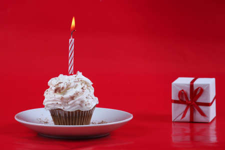 Birthday cupcake with a single candle on it on red background