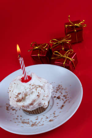 Birthday cupcake with a single candle on it on red background Stock Photo - 676484