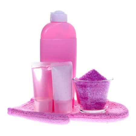 fregando: composici�n rosada del cuarto de ba�o con el jab�n l�quido, el gel de la ducha, la loci�n del cuerpo, la sal de ba�o y el guante que friega (aislados en el fondo blanco)