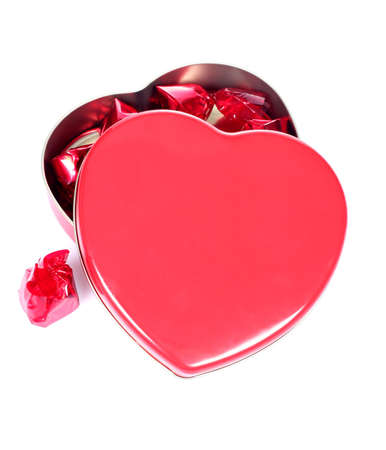 Close up of an open heart shaped gift box with chocolates (isolated on white background)