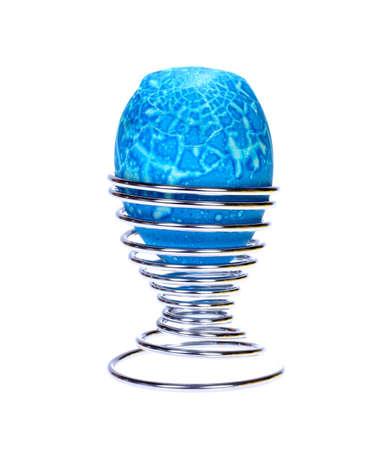 broken blue Easter Egg in stainless steel holder isolated on white background photo