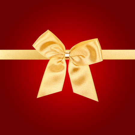 Gold Christmas bow on square red card photo