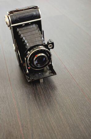 folding camera: antique camera on wooden floor