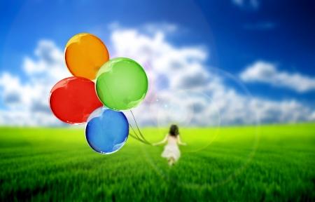 ni�o corriendo: Ni�o en una pradera verde jugando con globos de colores  Foto de archivo