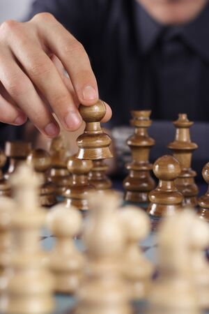 first move: Businessman playing chess game makes his first move Stock Photo