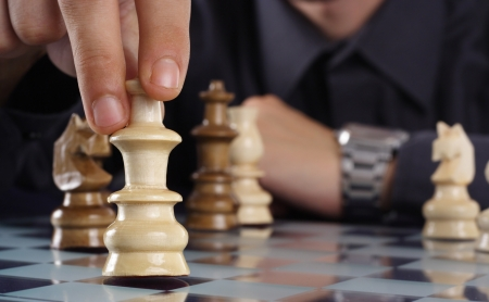 competitive business: Businessman playing chess game makes his move Stock Photo